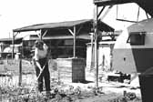 Vintage photo of a woman hoeing her garden near the camp trailers in the 1940's, at the Hanford Trailer Camp in Washington
