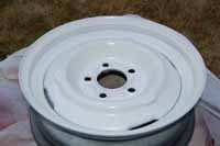 Photos shows the fully restored trailer wheel after we sanded and primed it and spray painted it using aerosol spray paint cans