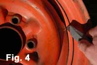Image is a close-up view that shows how to use a utility knife to clean out the welded joints befotre priming and spray painting the wheel