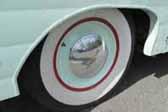 Photo shows an example of old fashioned full wheel covers on a vintage trailers wheels
