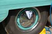 Image shows an example of a vintage trailer wheel painted light blue and with a pointy hubcap