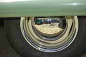 Great example of buttercup yellow wheels with a chrome hubcap and chrome beauty rings mounted on a vintage trailer painted green