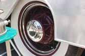 Photos shows old vintage wire wheels painted maroon and with a small hubcap, mounted on a vintage trailer from the 1950's