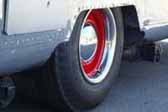 Example of beautiful red wheels with a small chrome baby moon hubcap mounted on a rare airstream vintage trailer