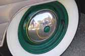 Photo shows a nice example of a vintage trailer wheel painted forest green with a chrome hubcap and wide whitewalls