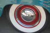 Image shows a restored vintage trailer with wheels painted red, and a chrome hubcap and beauty ring