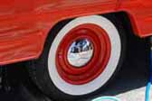 Great example of an orange vintage trailer wheel with a chrome hubcap and wide whitewall tire