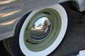 Nice example of olive green wheels with a small baby moon hubcap, on a vintage trailer