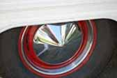 Photo shows red painted vintage trailer wheels with pointy hubcap and beauty rings