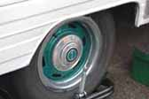 Photo provides a shot of modern wheels painted green, and with a small hubcap, mounted on a vintage travel trailer