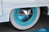 Picture shows an example of vintage trailer wheels painted sky blue and with a pointy chrome hubcap