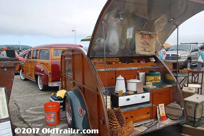 This vintage towing rig is a classic plymouth woodie station wagon pulling a Woodie teardrop trailer