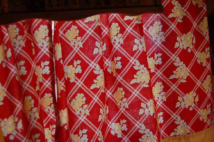 This photo shows a swatch of retro fabric with a country kitchen pattern on a red background, for your vintage trailer