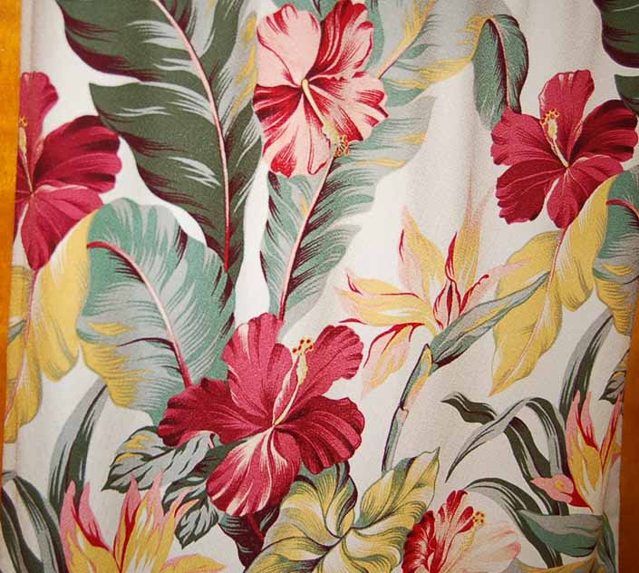 This photo shows a swatch of retro fabric with a hawaiian tropical flowers design on a white background, for your vintage trailer