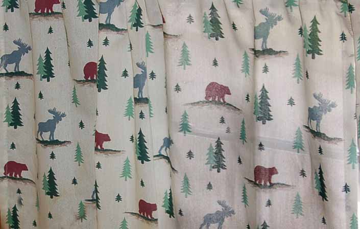 This photo shows a swatch of retro fabric with a moose, bear and pine tree cabin pattern, for your vintage trailer