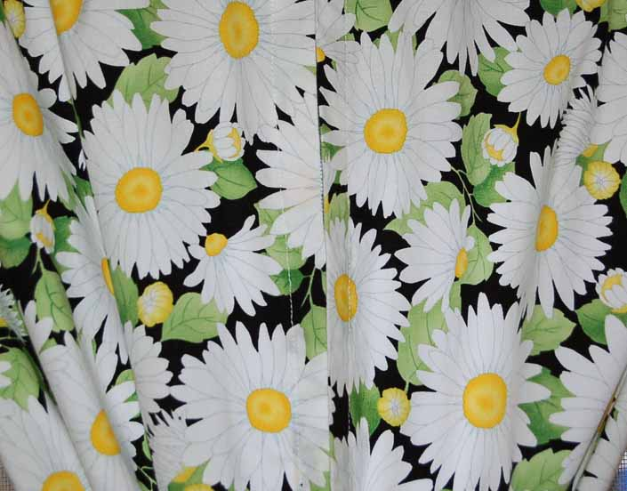 This photo shows a swatch of retro fabric with Bright Daisies on a Black Background pattern, for your vintage trailer