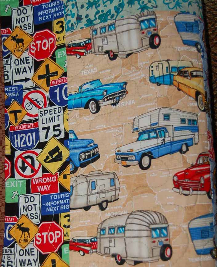 This photo shows a swatch of retro fabric with a vintage trailers, cars and trucks pattern
