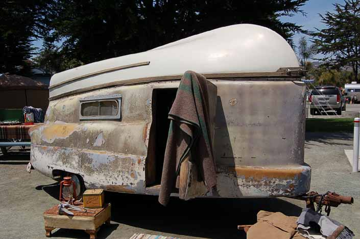 Original fiberglass boat attached to the roof of a rare vintage 1954 Kompak trailer
