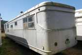 Photo of the rear end of a Spartan Manor trailer awaiting restoration in a vintage trailer junk yard