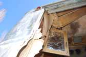 Photo shows an original cabinet door hanging in a rare Palace travel trailer stored in a vintage trailer junkyard