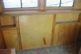 Photo shows original woodwork and cabinets in a restorable 1948 Westcraft Westwood Trailer